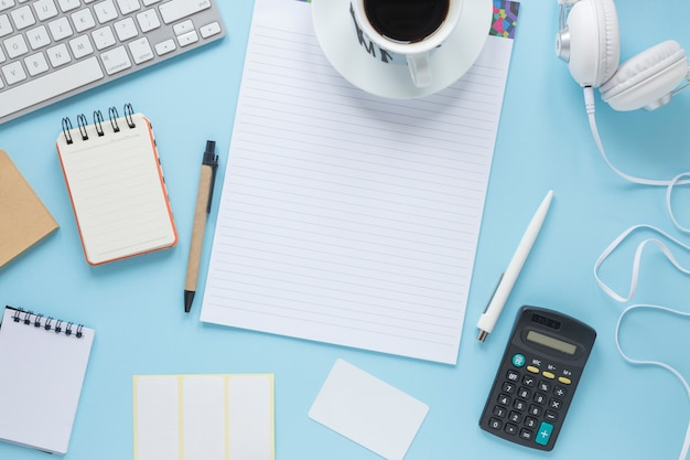 Coffee cup on single line page; spiral notepad; pen; keyboard; headphone against blue background Free Photo