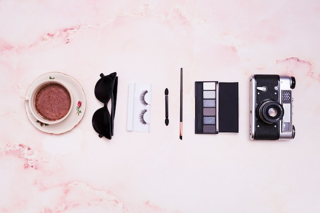 Coffee cup; sunglasses; eyelashes; makeup brush; eyeshadow palette and vintage camera on pink textured backdrop Free Photo