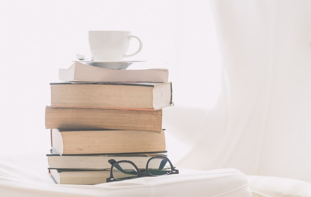 Coffee cup with book and eyeglasses Free Photo