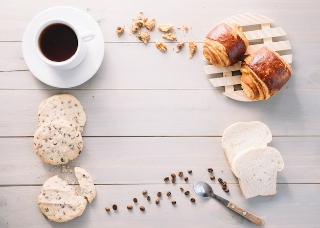 Coffee cup with buns and cookies on table Free Photo