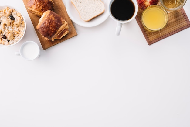 Coffee cup with buns and oatmeal on table Free Photo