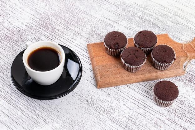木の板にチョコレートのマフィンとコーヒーカップ 無料写真