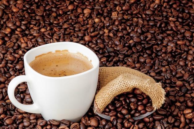 木製のテーブルの上のコーヒーバッグとコーヒーカップ。上から見る。 Premium写真