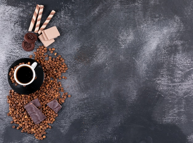 Coffee cup with coffee beans chocolate and cookies with copy space Free Photo