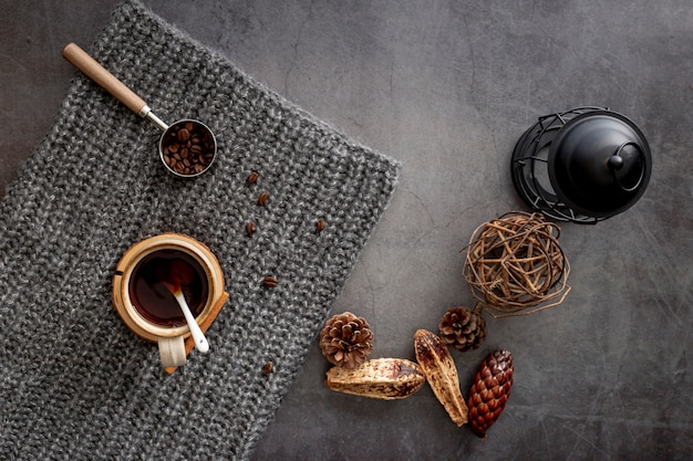 Coffee cup with coffee beans on a grey knitted scarf Free Photo