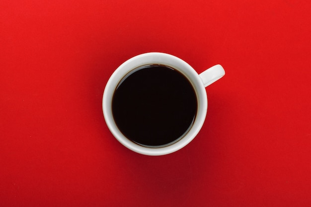 Coffee cup with coffee beans on red. Premium Photo