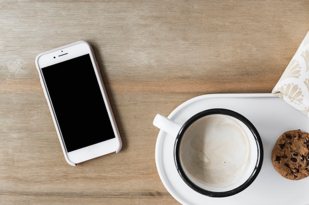 Coffee cup with cookie on white tray and smartphone on wooden backdrop Free Photo