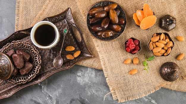 Coffee cup with dates fruit and almonds on metallic tray Free Photo