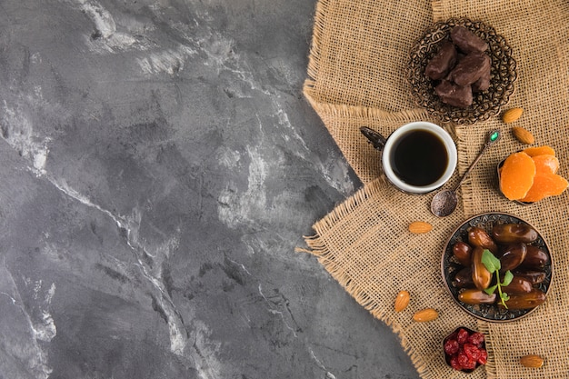 Coffee cup with dates fruit and almonds Free Photo