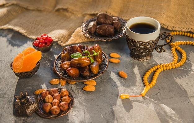 Кофейная чашка с финиками, фруктами и орехами Premium Фотографии