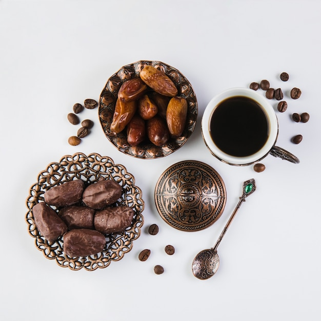 Coffee cup with dates fruit on table Free Photo