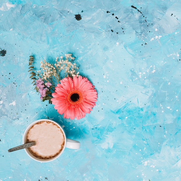 Coffee cup with flowers on blue table Free Photo
