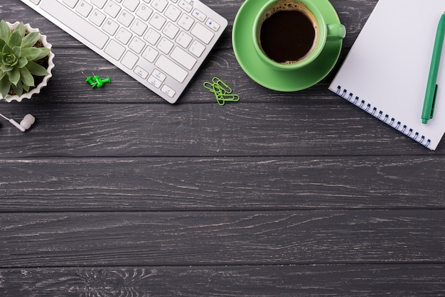 Coffee cup with keyboard and notebook on wooden desk Free Photo
