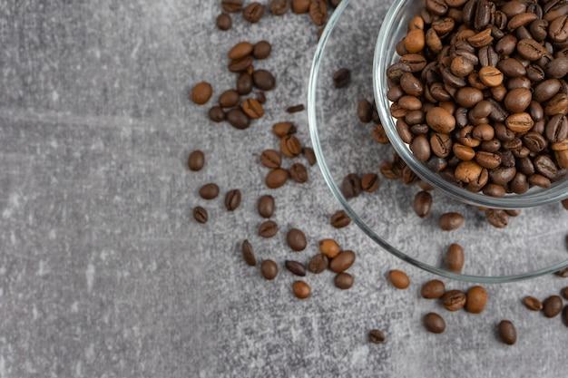 Чашка кофе с жареными бобами на сером фоне камня. вид сверху, плоская планировка с местом для текста Premium Фотографии