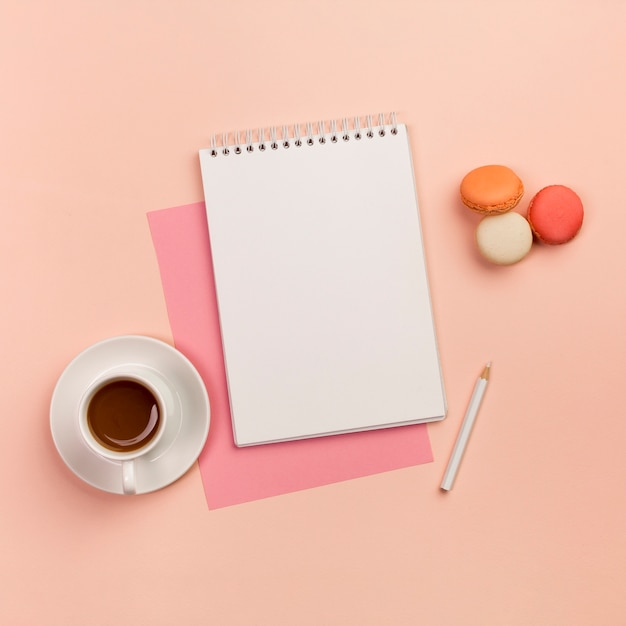 Coffee cup with spiral notepad,white pencil and macaroons on colored backdrop Free Photo