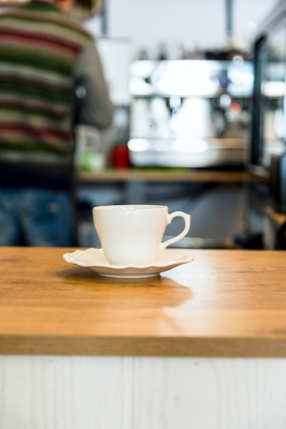Coffee cup on wooden table over defocused cafeteria background Free Photo
