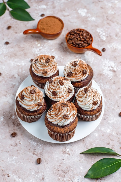 Кофейные кексы украшены взбитыми сливками и кофейными зернами. Бесплатные Фотографии