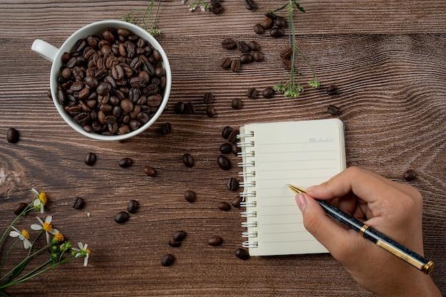 コーヒーカップとコーヒー豆のテーブル、国際的なコーヒーのコンセプトの日。 無料写真