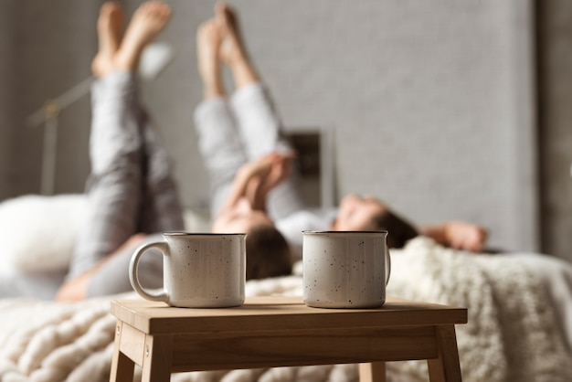 Coffee cups on the table with couple behind in bed Free Photo