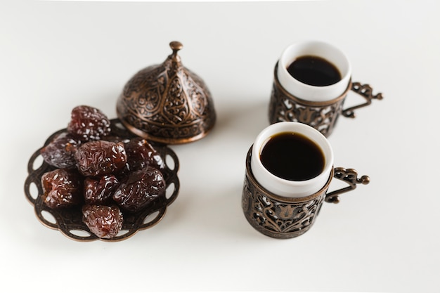 Coffee cups with dates on saucer Free Photo