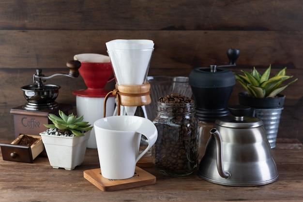 Кофейный набор с, жареные бобы, чайник, кофемолка, белая чашка и цветочный горшок на деревянный стол и фон Premium Фотографии