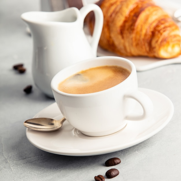 Coffee espresso in white cup with milk, jam and croissants. Premium Photo