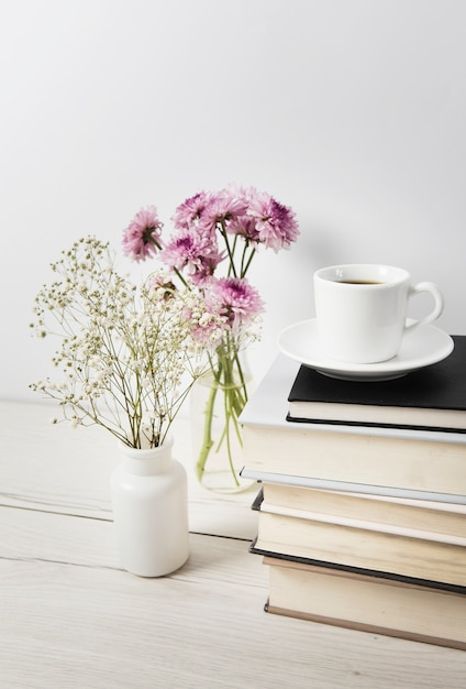 Coffee and flowers on plain background Free Photo