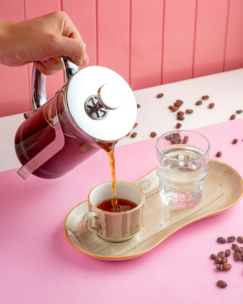 Coffee in french press with glass of water and coffee beans on table Free Photo