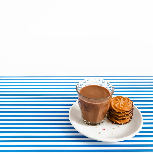 Coffee glass and stack of cookies on plate over white and stripes backdrop Free Photo