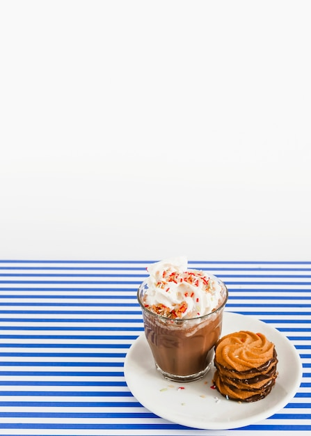 Coffee glass with whipped cream and stack of cookies on plate over stripes backdrop Free Photo