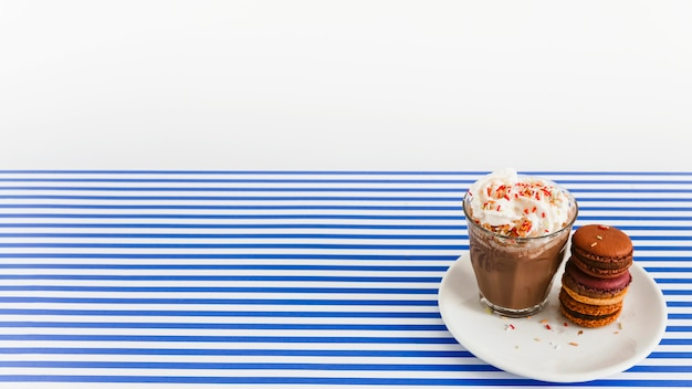 Coffee glass with whipped cream and stack of macaroons on plate over backdrop Free Photo