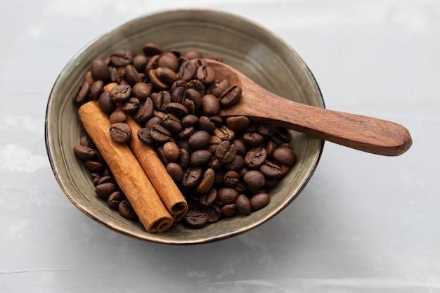 小さなボウルに木のスプーンでコーヒーの穀物とシナモン Premium写真