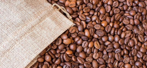コーヒーの粒がバッグから飛び散ります。コーヒー豆の背景。 Premium写真
