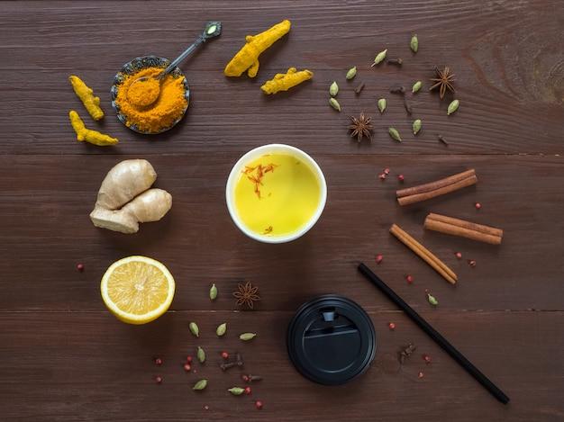 ウコン、シナモン、生姜、レモン、コショウで紙コップにコーヒー。抗ウイルス感染の予防。コピースペース、トップビュー Premium写真