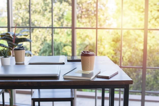紙コップのコーヒー、オフィスの木製テーブルの上のラップトップとノート Premium写真
