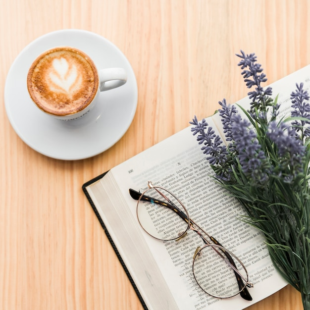 Coffee latte,lavender flower,spectacles and notebook on wooden desk Free Photo