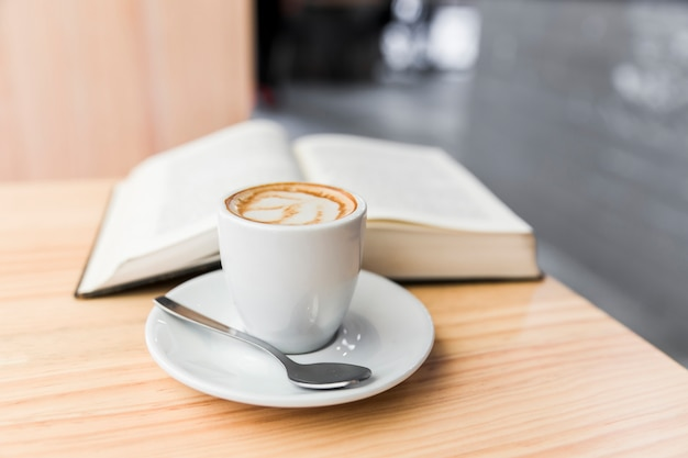 Coffee latte and open book on wooden desk Free Photo