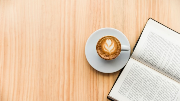 Coffee latte and open book on wooden surface Free Photo