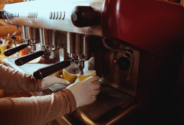 Coffee machine pourig coffee to yellow cardboard coffee cup in bar. cropped image. closeup Premium Photo