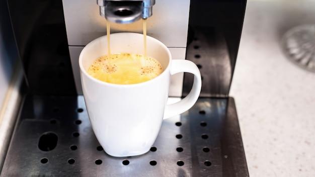 Macchina da caffè versando il caffè con in una tazza Foto Gratuite