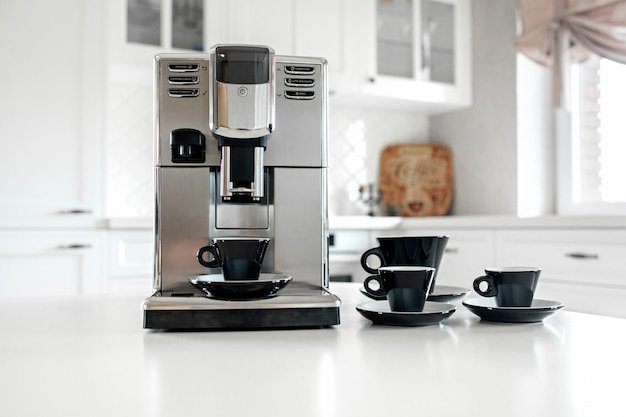 Coffee machine with cups for espresso on the kitchen table. close-up Premium Photo