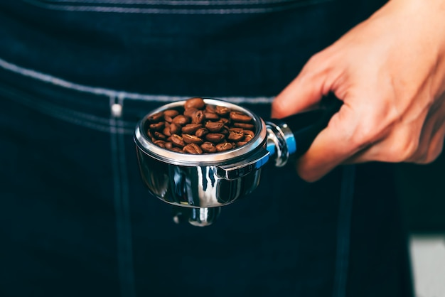The coffee maker holds a device that contains coffee beans, preparing coffee for customers. Premium Photo