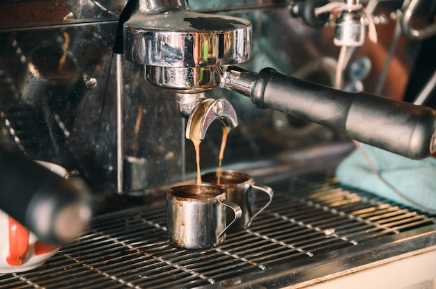 Coffee maker machine grinder pouring coffee in mug Premium Photo