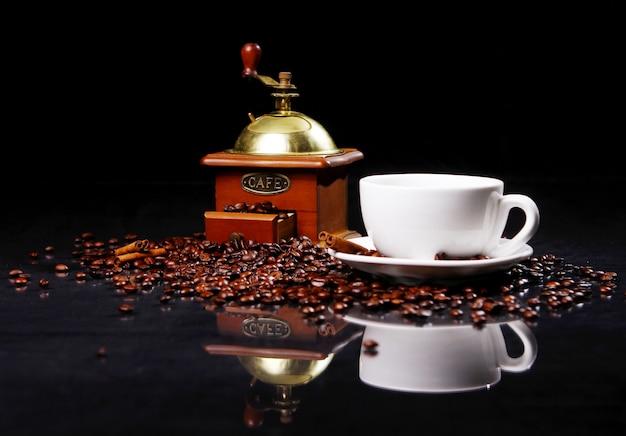 Кофемолка на столе с кофейными зернами вокруг Бесплатные Фотографии