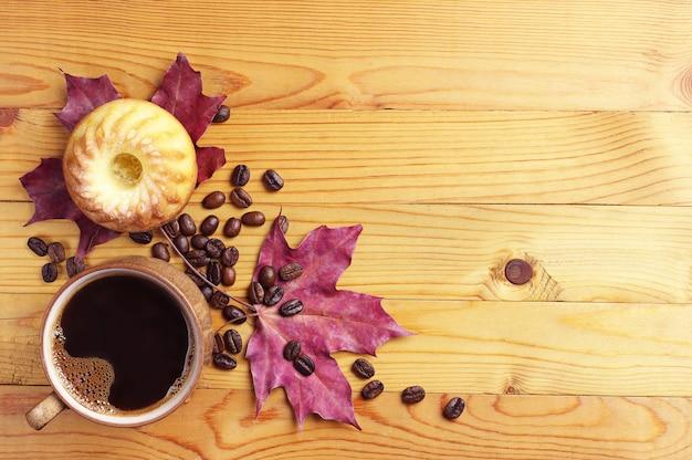 Кофе, кексы и осенние листья на деревянном столе Premium Фотографии