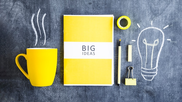 Coffee mug; big ideas; stationery and drawn light bulb on chalkboard Free Photo