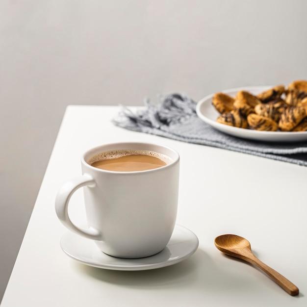 Кофейная кружка на столе с печеньем на тарелке и ложке Бесплатные Фотографии
