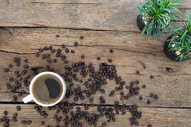コーヒーマグとコーヒー豆は机の上にあります Premium写真