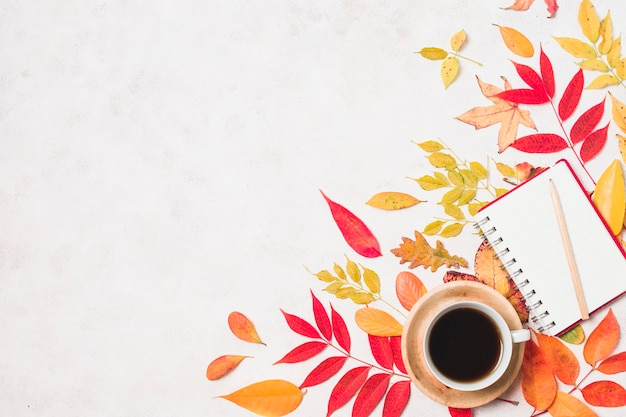 Coffee and notebook with autumn leaves copy space Free Photo