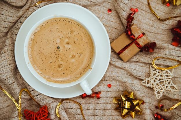 ギフトや休日の弓とニット生地の背景にコーヒー Premium写真